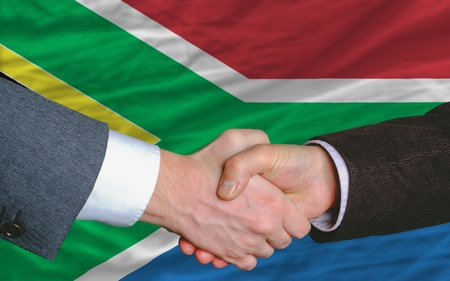two businessmen shaking hands after good business investment  agreement in south africa, in front of flag photo