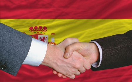entrepeneur: two businessmen shaking hands after good business investment  agreement in spain, in front of flag
