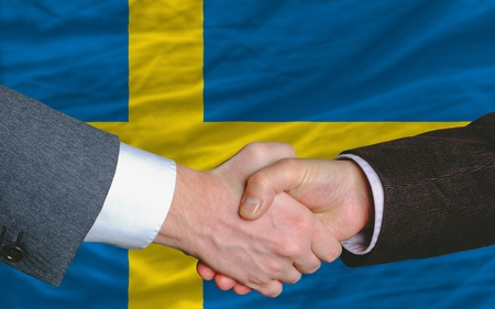 two businessmen shaking hands after good business investment  agreement in sweden, in front of flag photo