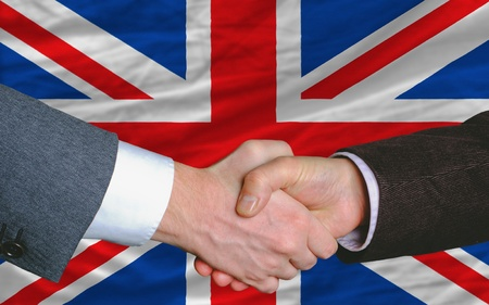 syndicate: two businessmen shaking hands after good business investment  agreement in united kingdom, in front of flag Stock Photo
