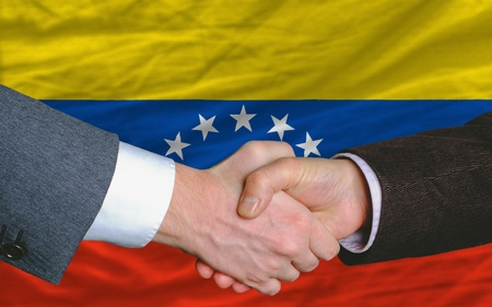entrepeneur: two businessmen shaking hands after good business investment  agreement in venezuela, in front of flag