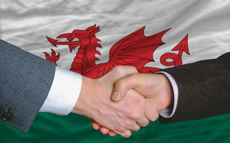 entrepeneur: two businessmen shaking hands after good business investment  agreement in wales, in front of flag