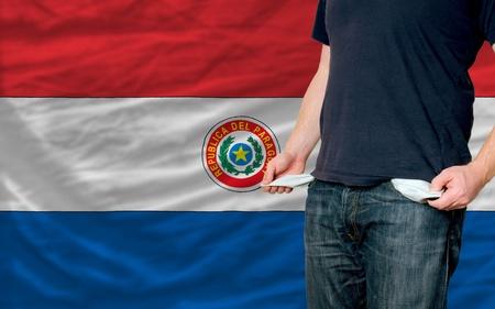 bandera de paraguay: pobre hombre mostrando los bolsillos vac�os delante de la bandera de Paraguay Foto de archivo