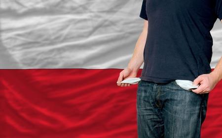 hombre pobre: pobre hombre mostrando los bolsillos vac�os delante de bandera de Polonia