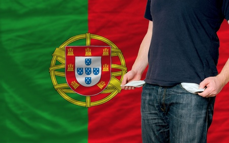 poor man showing empty pockets in front of portugal flag photo