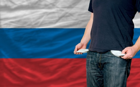 poor man showing empty pockets in front of russia flag photo