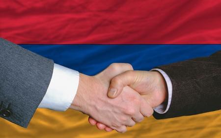 buen trato: hombres de negocios apret�n de manos tras mucho delante de la bandera de Armenia