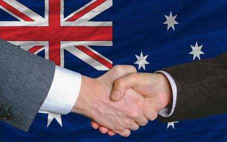 buen trato: hombres de negocios apret�n de manos tras mucho delante de la bandera de Australia