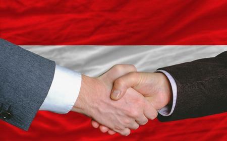 buen trato: hombres de negocios apret�n de manos tras mucho delante de austria bandera