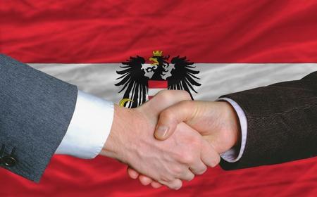 buen trato: hombres de negocios apret�n de manos despu�s de mucho frente a la bandera de austria Foto de archivo