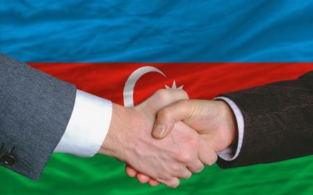 buen trato: hombres de negocios apret�n de manos tras mucho delante de la bandera de Azerbaijan