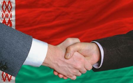 deal in: businessmen handshakeafter good deal in front of belarus flag Stock Photo