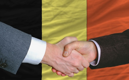 deal in: businessmen handshakeafter good deal in front of belgium flag