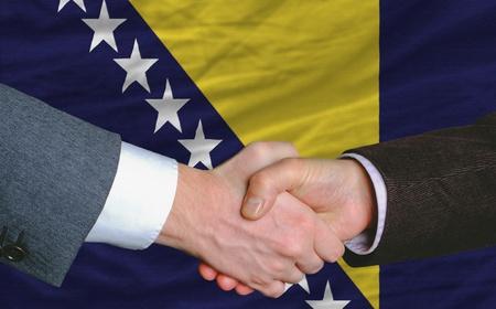 buen trato: hombres de negocios apret�n de manos despu�s de mucho frente a Bosnia y Herzegovina Bandera