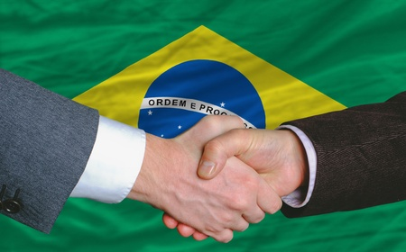 brazil country: businessmen handshake after good deal in front of brazil flag