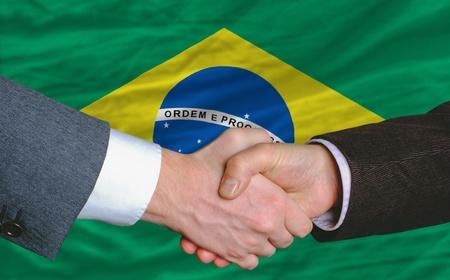 businessmen handshake after good deal in front of brazil flag