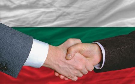 buen trato: hombres de negocios apret�n de manos tras mucho delante de la bandera de Bulgaria Foto de archivo