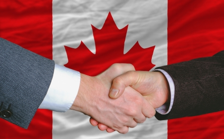 canada flag: businessmen handshakeafter good deal in front of canada flag