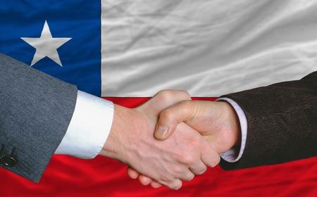 buen trato: empresarios handshakeafter mucho frente a la bandera de Chile