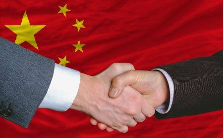 businessmen handshakeafter good deal in front of china flag photo