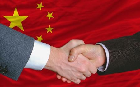 investors: businessmen handshakeafter good deal in front of china flag