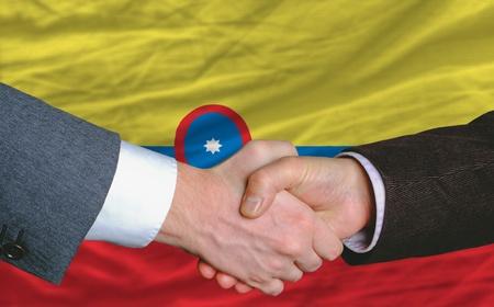 buen trato: empresarios handshakeafter mucho frente a la bandera de Colombia