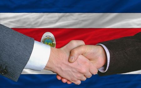buen trato: empresarios handshakeafter mucho frente a la bandera costarica Foto de archivo