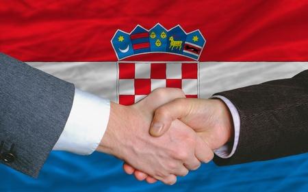 buen trato: empresarios handshakeafter mucho delante de la bandera de Croacia Foto de archivo