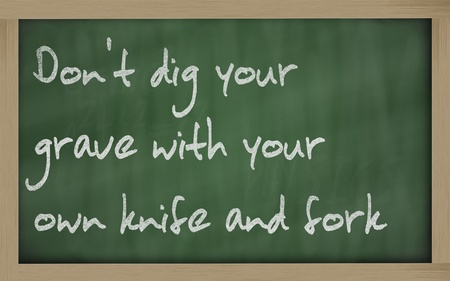 wriiting: Blackboard writings Dont dig your grave with your own knife and fork Stock Photo