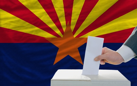 man putting ballot in a box during elections  in front of flag american state of arizona Stock Photo - 11982926