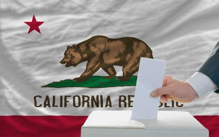man putting ballot in a box during elections  in front of flag american state of california Stock Photo - 11982841