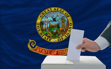 man putting ballot in a box during elections  in front of flag american state of idaho photo