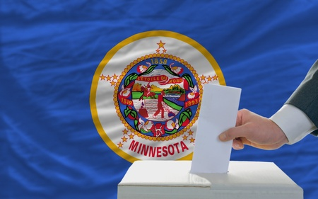 ballot box: man putting ballot in a box during elections  in front of flag american state of minnesota Stock Photo