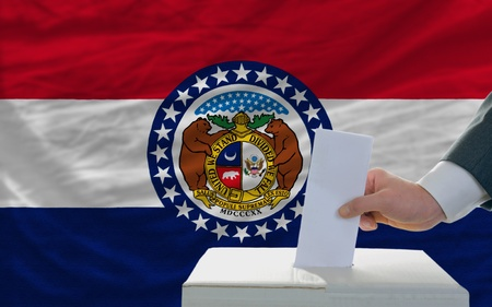 ballot box: man putting ballot in a box during elections  in front of flag american state of missouri
