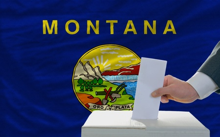 man putting ballot in a box during elections  in front of flag american state of montana photo