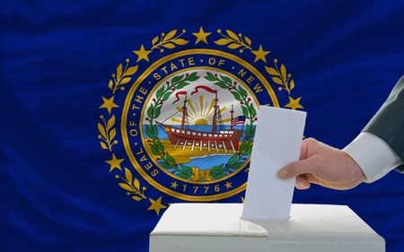 man putting ballot in a box during elections  in front of flag american state of new hampshire photo
