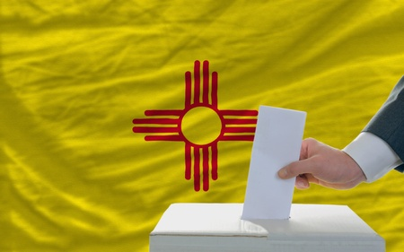 man putting ballot in a box during elections  in front of flag american state of new mexico photo