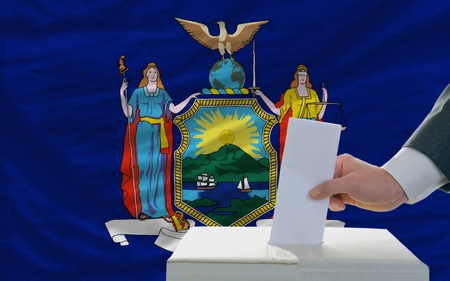 man putting ballot in a box during elections  in front of flag american state of new york photo