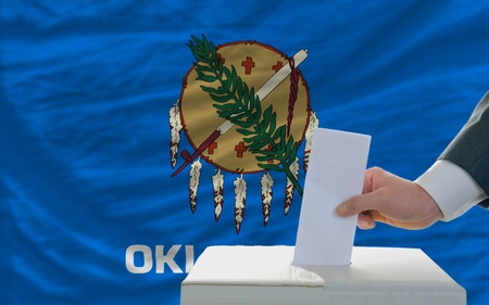 man putting ballot in a box during elections  in front of flag american state of oklahoma photo