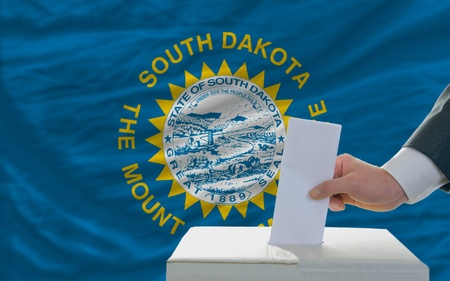 man putting ballot in a box during elections  in front of flag american state of south dakota photo