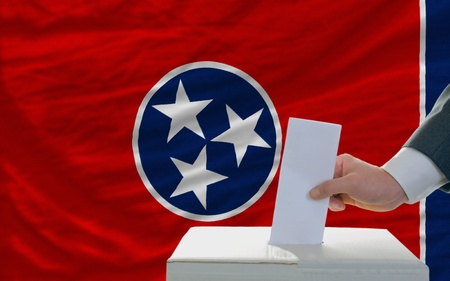 man putting ballot in a box during elections  in front of flag american state of tennessee photo