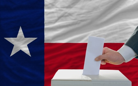man putting ballot in a box during elections  in front of flag american state of texas photo