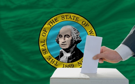 man putting ballot in a box during elections  in front of flag american state of washington photo