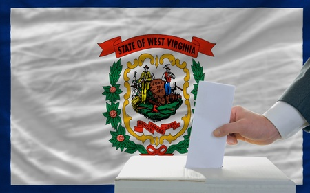 man putting ballot in a box during elections  in front of flag american state of west virginia photo