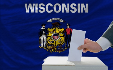 wisconsin flag: man putting ballot in a box during elections  in front of flag american state of wisconsin Stock Photo