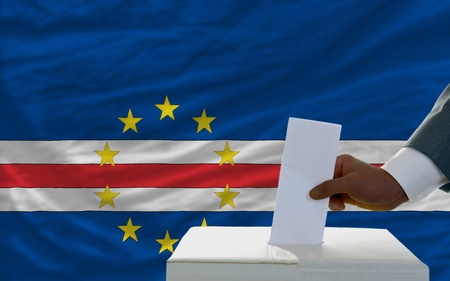man putting ballot in a box during elections  in front of national flag of capeverde photo