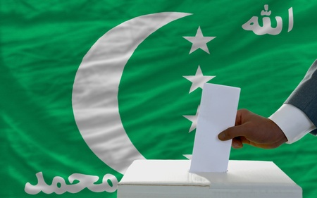 man putting ballot in a box during elections  in front of national flag of comoros photo