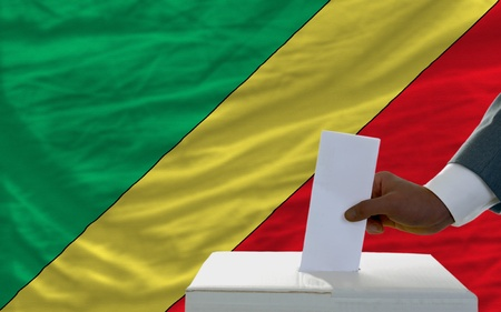 man putting ballot in a box during elections  in front of national flag of congo photo
