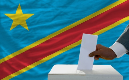 parliamentary: man putting ballot in a box during elections  in front of national flag of congo Stock Photo