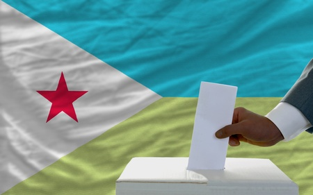 man putting ballot in a box during elections  in front of national flag of djibuti photo